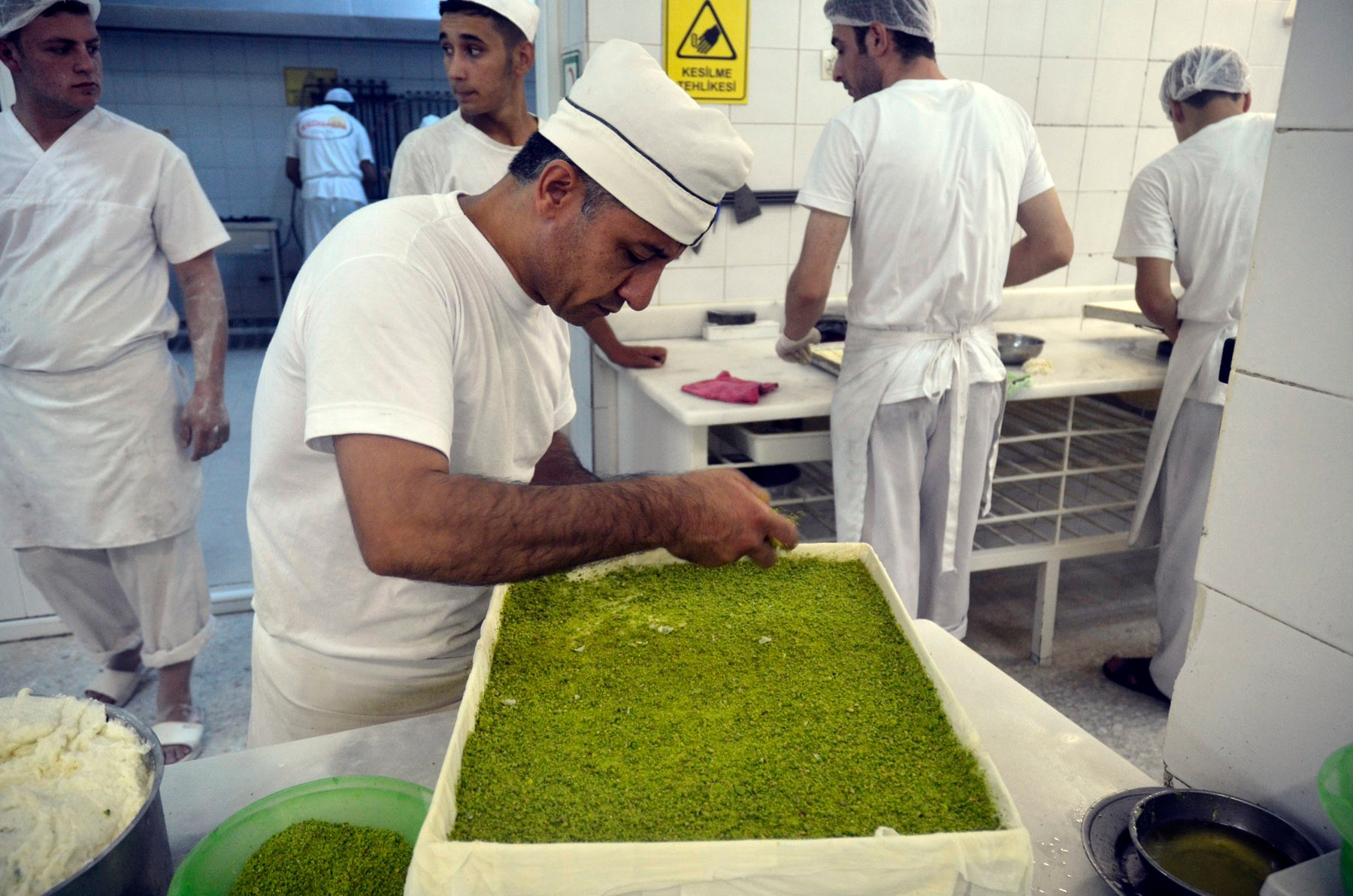 A man sprinkles pistachio over a layer of cream to make the filling
