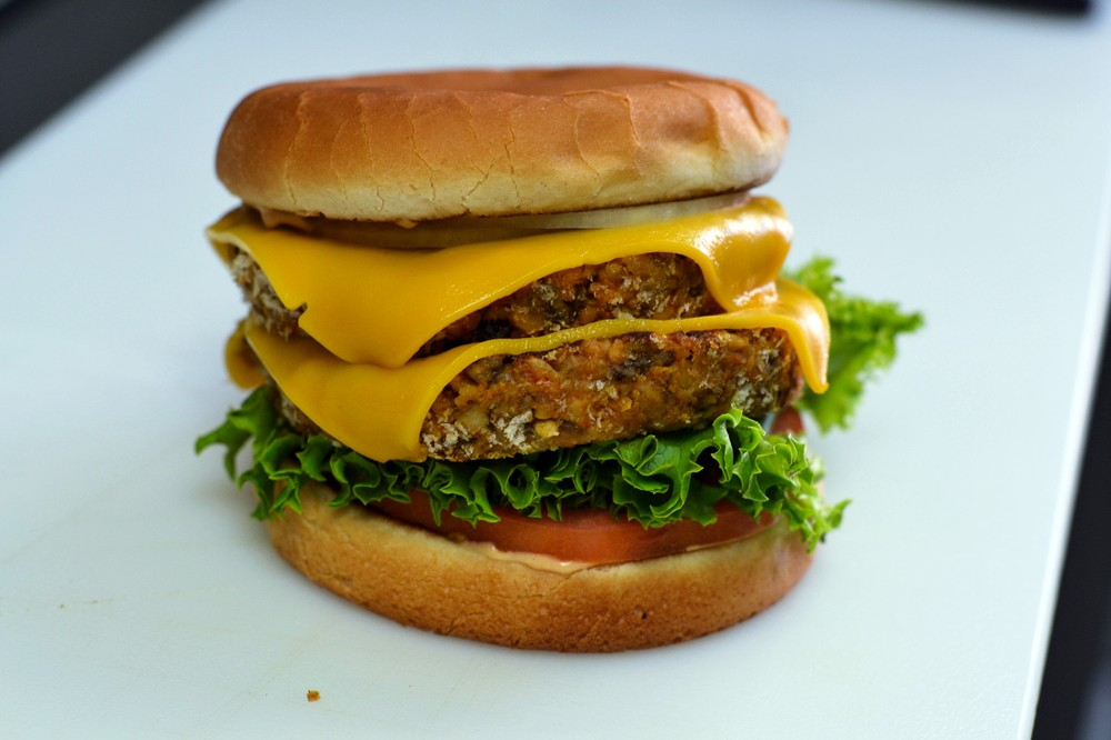 A towering double vegan cheeseburger with vegan American cheese and vegan thousand island