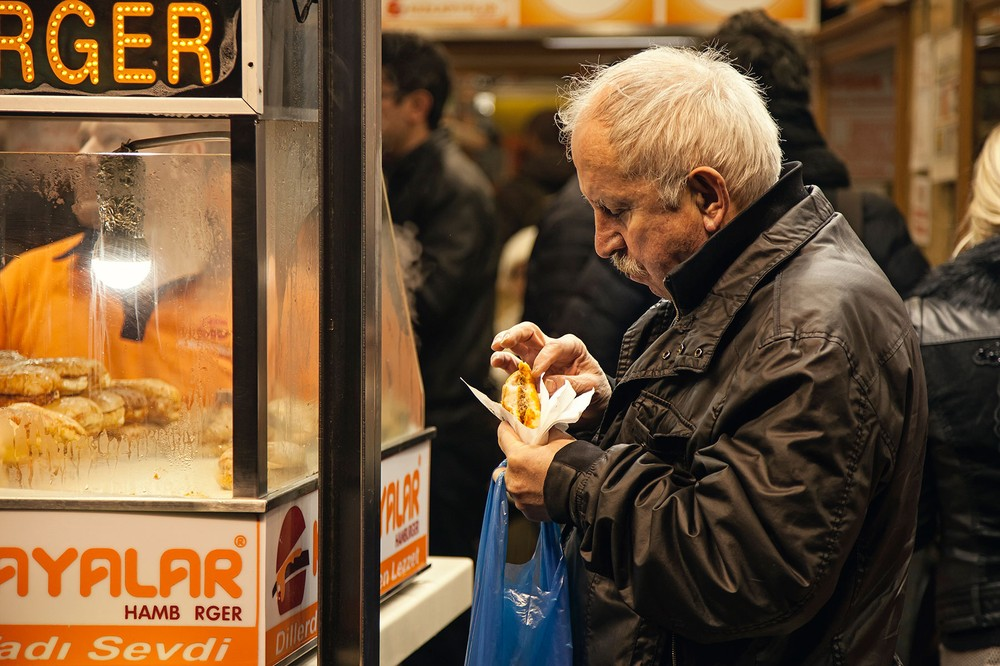 An-old-man-from-Istanbul-eating-his-islak-burger-in-front-of-the-Bambi-Cafe