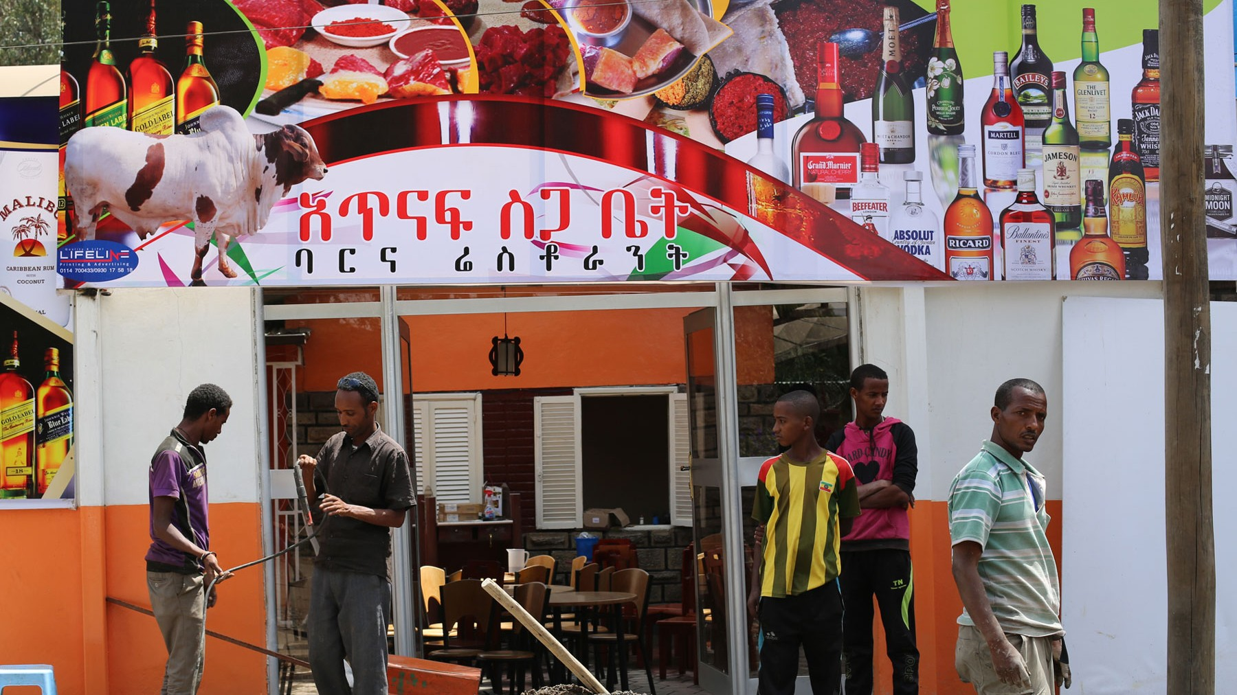 Atnaf-siga-bet-put-the-finishing-touches-on-their-new-sign.-Where-it-showed-fish-and-vegetables-yesterday-today-they-advertise-raw-meat-and-alcohol