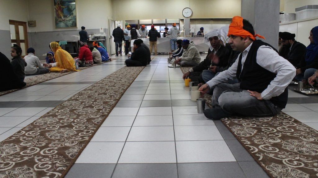 People sitting down to eat in the Langar hall
