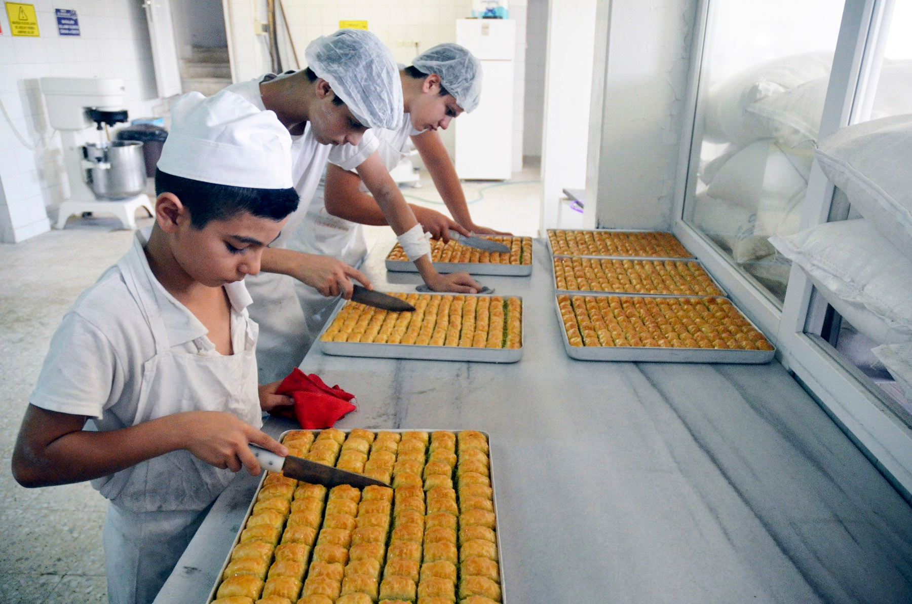 The young apprentinces make sure the baklava is well cut after its baked