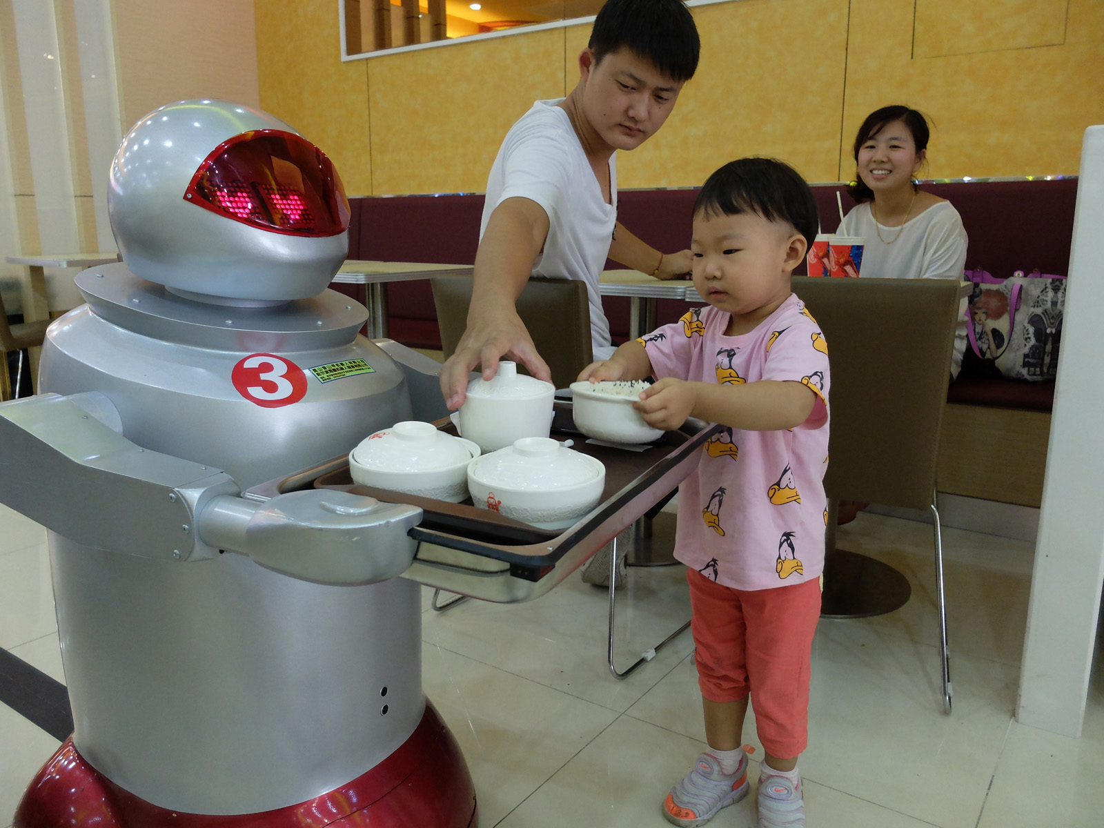 Toddler with robot waiter