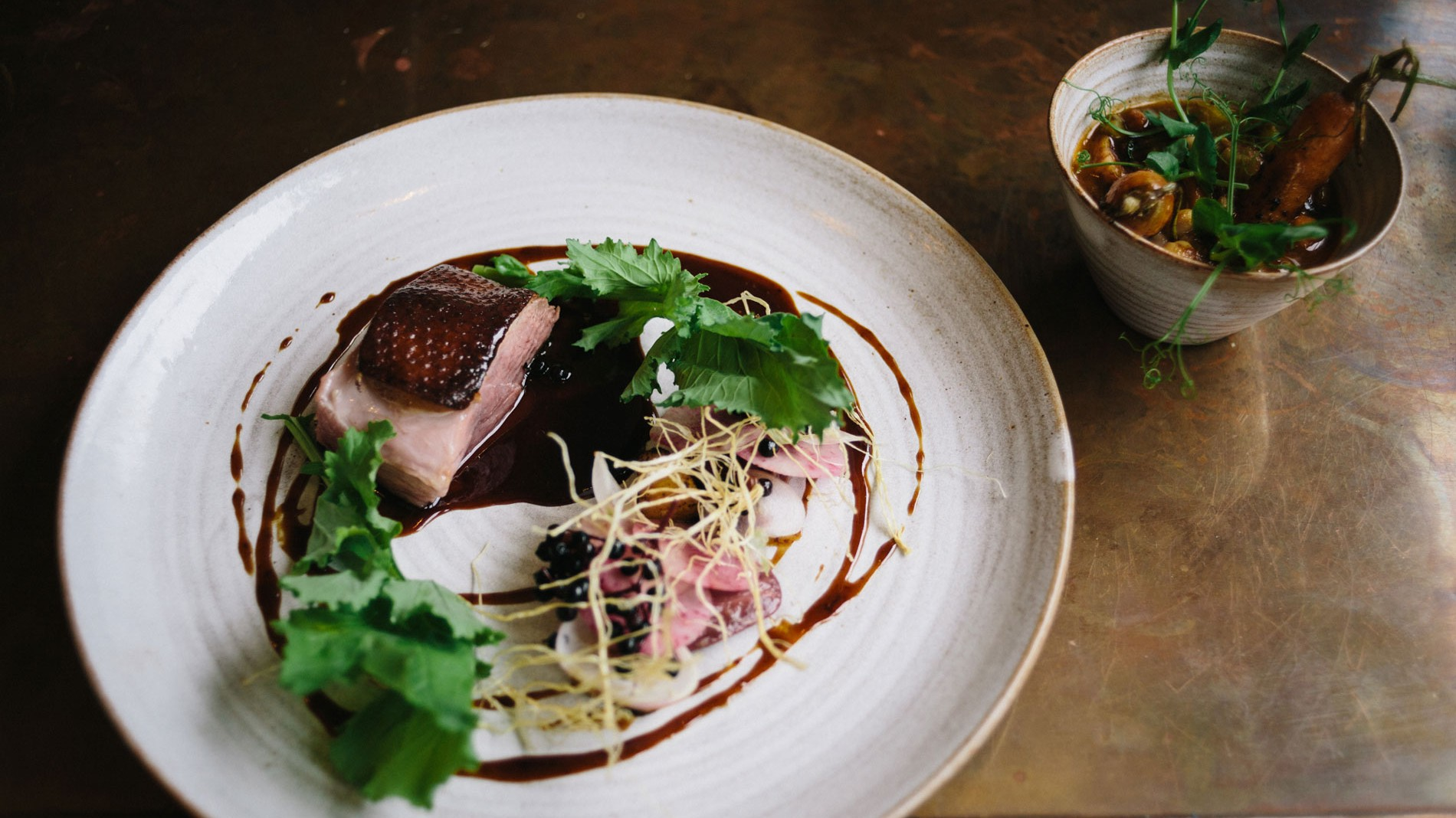 pidgin-Smoked-duck-breast,-smoked-confit-duck-leg-and-neck-cassoulet,-with-pickled-elderberries,-koji-parsnips,-turnips,-and-radishes